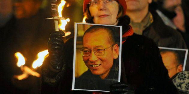 Une femme tient le portrait de Liu Xiaobo lors d'une procession en son honneur après la cérémonie des...