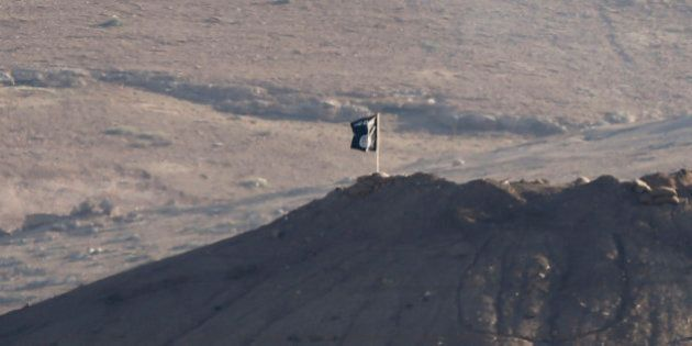 A black flag belonging to the Islamic State is seen near the Syrian town of Kobani, as pictured from...