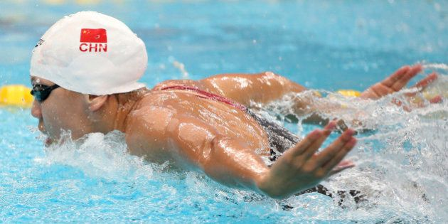 China's Chen Xinyi swims in her women's 100m butterfly heat at the 17th Asian Games in Incheon, South...