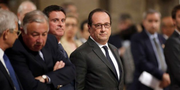 French President Francois Hollande, right, stands next to his Prime Minister Manuel Valls before a mass...