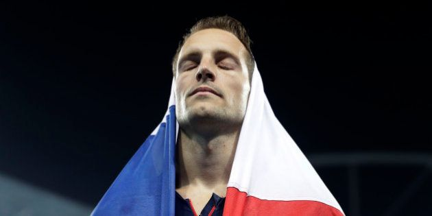 France's Renaud Lavillenie is covered in a French flag as he leaves the stadium after taking the silver...