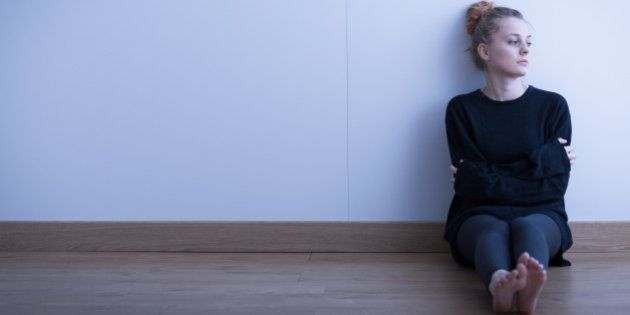 Lonely thoughtful girl sitting on the floor