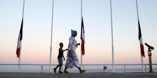 A woman and her child pass by French flags at half mast near the site of a deadly attack on the famed...