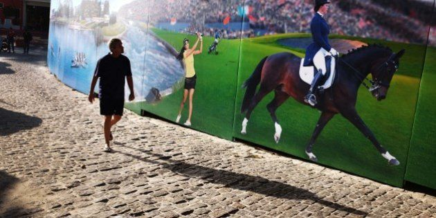 A pedestrian walks by a mural of Russian Olympic athletes on Copacabana beach Monday, Aug. 1, 2016, in...