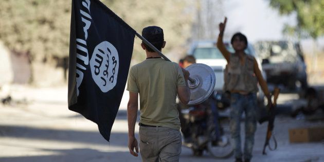 Un membre des forces rebelles syriennes retire un drapeau de l'EI au nord d'Alep, en Syrie, le 7 octobre