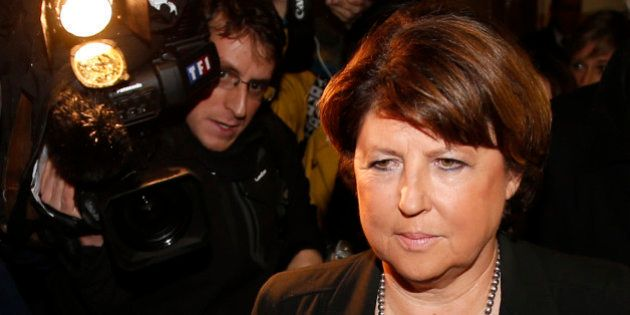 Lille Mayor Martine Aubry is surrounded by journalists as she leaves after a meeting at luxury and sports...