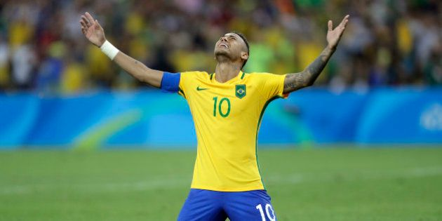 Brazil's Neymar cries as he kneels down to celebrate after scoring the decisive penalty kick during the...
