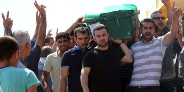 People carry a victim's coffin as they attend funeral services for dozens of people killed in last night's...