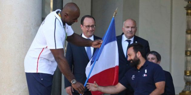 French President Francois Hollande (2ndL) stands next to France's Olympic and World judo champion Teddy...