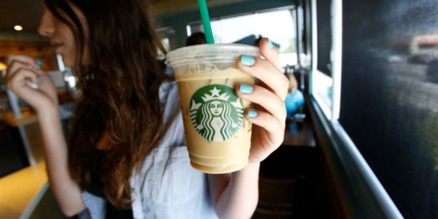 A patron holds an iced beverage at a Starbucks coffee store in Pasadena, California July 25, 2013. Starbucks...