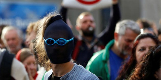 A masked demonstrator protests outside a congress centre where negotiators are expected to discuss the...