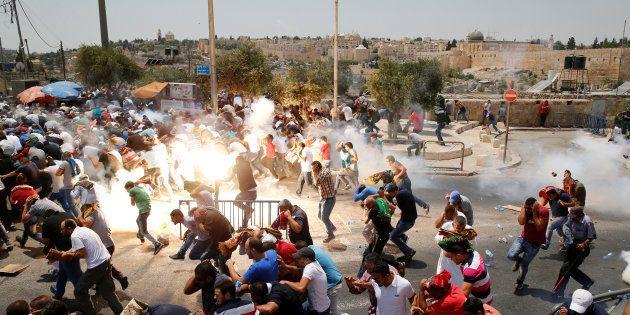 Des Palestiniens courent après des tirs de gaz lacrymogènes de la police israélienne après la prière...