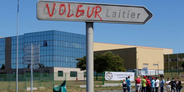 French dairy farmers from the FNSEA union gather as they block the round-about access to the Lactalis...