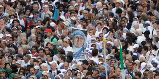 Faithful and pilgrims wait to enter in St. Peter's Square at the Vatican before a canonization ceremony,...