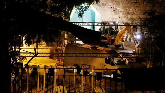 Des forces de sécurité israéliennes enlevant les détecteurs de métaux récemment installés à une entrée...