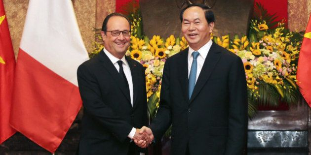 France's President Francois Hollande, and his Vietnamese counterpart Tran Dai Quang shake hands as they...