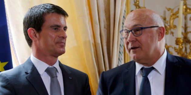 French Prime Minister Manuel Valls (L) and French Finance Minister Michel Sapin attend a ceremony at...