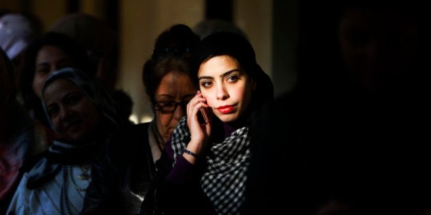 An Egyptian woman talks on her mobile phone while waiting to to vote in Maadi, a suburb of Cairo, Egypt,...