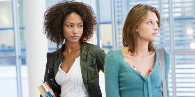 Two women looking away with books in hand at university