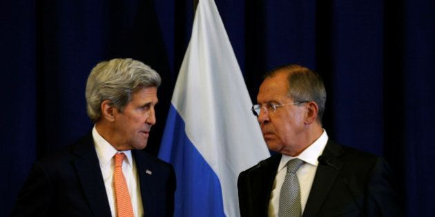 U.S. Secretary of State John Kerry and Russian Foreign Minister Sergei Lavrov (R) look toward one another...