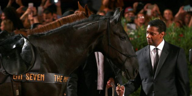 Actor Denzel Washington poses with horses during the red carpet of the