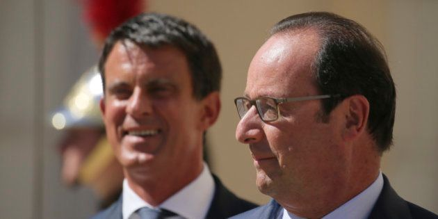 French President Francois Hollande (R) speaks with Prime Minister Manuel Valls before a meeting with...