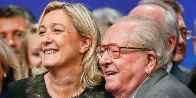 Marine Le Pen (L), France's National Front political party leader, reacts with her father Jean-Marie...