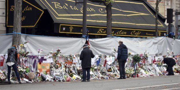 People mourn in front of the screened-off facade of the Bataclan Cafe adjoining the concert hall, one...