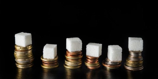 Piles of coins with sugar cubes and bottles filled with sugar on top, symbolising sugar tax, on black slate background