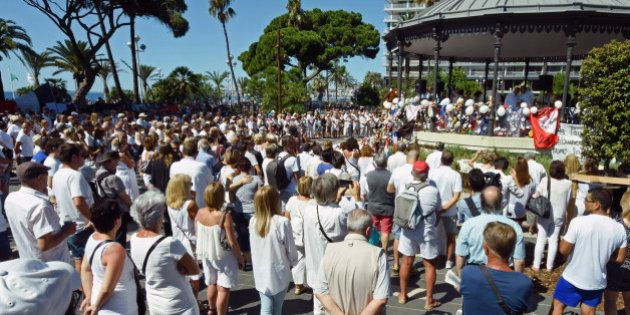 People, including local residents, wear white as they gather to pay respects for the victims of the July...