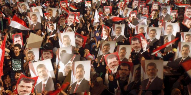 Members of the Muslim Brotherhood and supporters of Egypt's President Mohamed Mursi hold pictures of...
