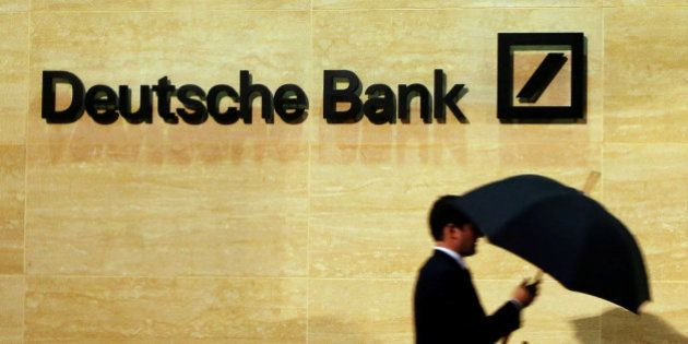 A man walks past Deutsche Bank offices in London December 5, 2013. REUTERS/Luke MacGregor/File