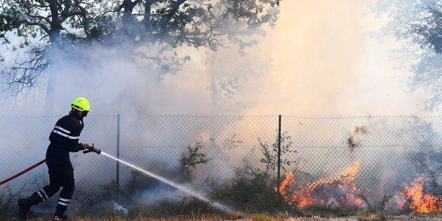Un pompier tente d'éteindre l'incendie d'Artigues, le 25 juillet, qui a connu