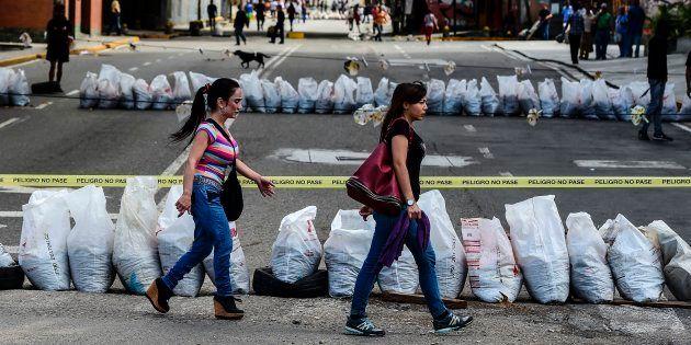 Des femmes traversent une rue bloquée par des manifestants anti-Maduro à Caracas, le 26