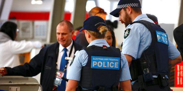 La police fédérale australienne contrôle des passagers à l'aéroport de Sydney, le 30