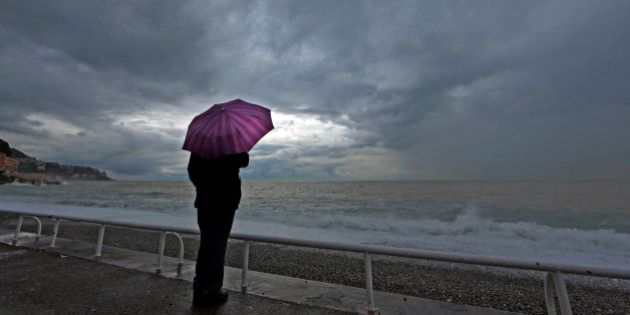 A woman protects herself under an umbrella during an autumn day on the Promenade Des Anglais in Nice...