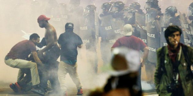 People maneuver amongst tear gas in uptown Charlotte, NC during a protest of the police shooting of Keith...