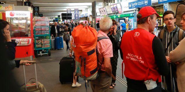 Des voyageurs parlent avec un employé de la SNCF en gare de Montparnasse, le 30