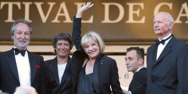 L'actrice Jeanne Moreau fait signe au public lors du 56ème festival de Cannes, entourée du Président...