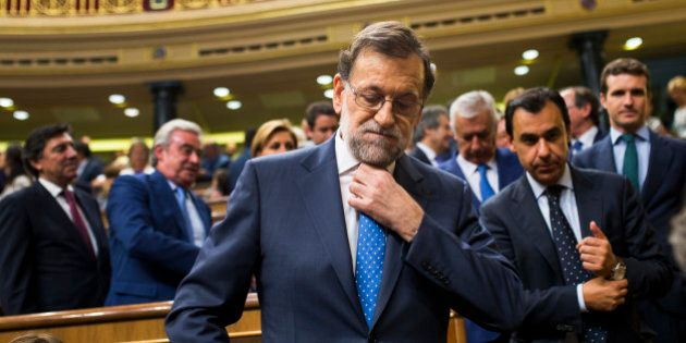 Spain's acting Prime Minister and Popular Party leader Mariano Rajoy adjusts his tie as he leaves at...