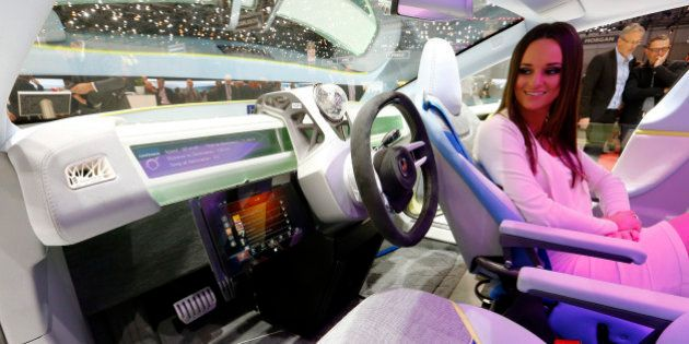 A model poses in the Rinspeed XchangE electric powered autonomous driving concept car is pictured during...