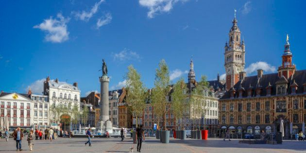 Grand Place with the Belfry tower of the Chamber of Commerce and the statue of the Column of the Goddess...