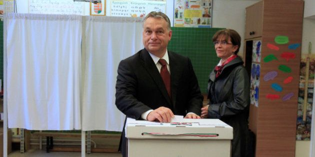 Hungary's Prime Minister Viktor Orban casts his ballot next to his wife Aniko Levai inside a polling...