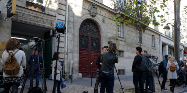 Journalists stand in front of the entrance of a luxury residence on the Rue Tronchet in central Paris,...