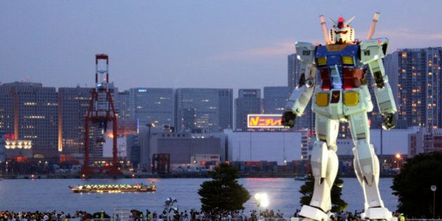 In this photo taken on July 11, 2009, people crowd to see 18-meter (60-foot) tall Gundam at a park in...