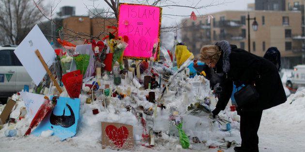 Une femme dépose des fleurs sur un mémorial près du lieu de la fusillade à Québec, le 31