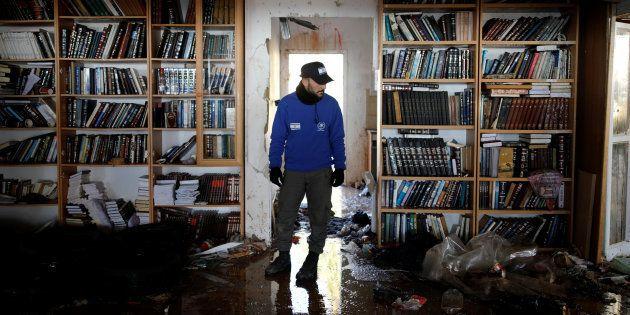 Un policier israélien inspecte une synagogue lors du deuxième jour de l'évacuation de la colonie d'Amona,...