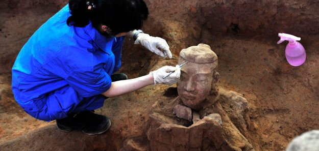 A member of an archaeology team unearths the head of a terracotta warrior at the excavation site inside...