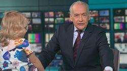 Une petite fille escalade le bureau d'un présentateur télé en plein