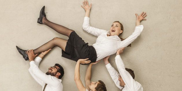 Business people carrying businesswoman in